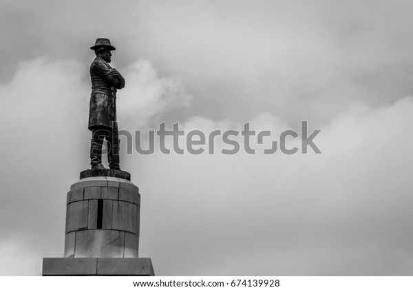 Detail of the statue of confederate General Robert E Lee in New Orleans in a greyscale image on a cloudy sky with copy space