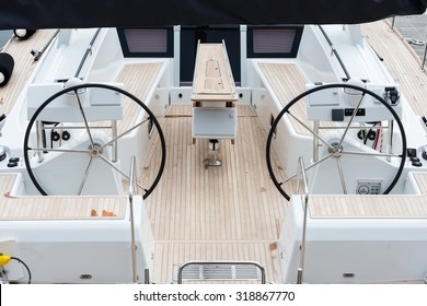 Detail of the steering wheels and symmetry in the deck of a luxury sail yatch.