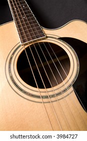 Detail of stings, sound hole and cutaway on acoustic guitar.