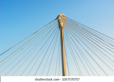 Detail of the structure of a cable-stayed bridge with the column and the guy wires isolated on a blue sky