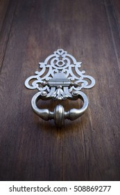 Detail of a stylish bronze knocker on a wooden door