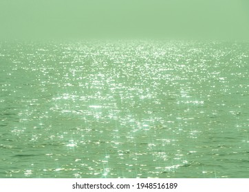 Detail of a sunlight reflecting in glittering sea. sparkling in water - background. sea water with sun glare and ripple. Powerful and peaceful nature concept.