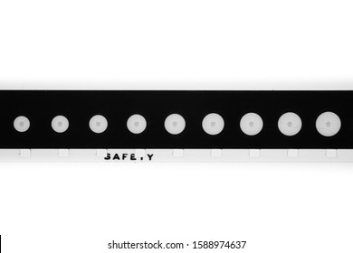 Detail of super 8 mm film strip black and white movie leader  tail with round shape and safety text on perforation gauge cinema background