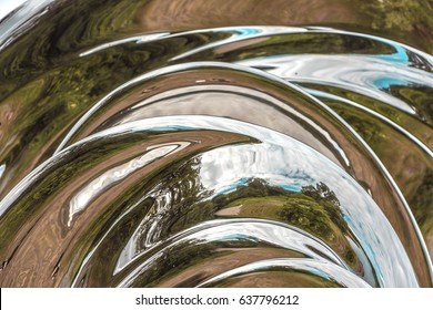 Detail of the surface of metal sculpture. Beautiful abstract texture of the metal construction as background for design. Trees reflected in modern art object. Full frame. Curved distorted reflections.