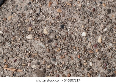 Detail of surface texture with small pebble rock on gravel background