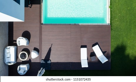 Detail of the swimming pool with deckchairs and lawn from above. Nobody inside