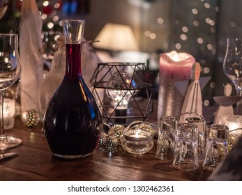 Detail of table decorated for Christmas with carafe of red wine. Shallow depth of field with wine and glasses in focus.