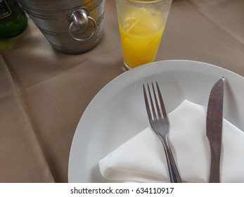 Detail of Table with white plate and cutlery in steel on white napkin and glass with juice