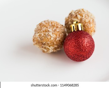Detail of tasty homemade walnut balls on white plate with flashy glitter and shiny red christmas ornament