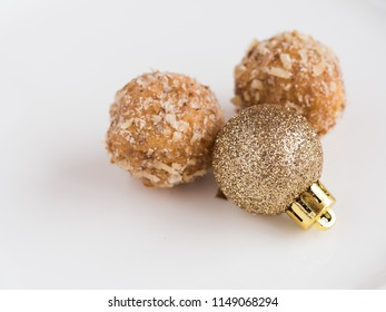 Detail of tasty homemade walnut balls on white plate with flashy and shiny red christmas ornament