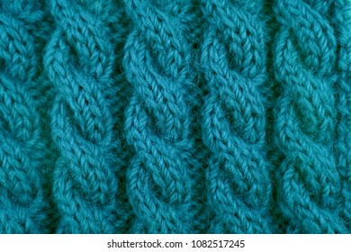 Detail of teal handknit coiled rope cable knitting stitch
