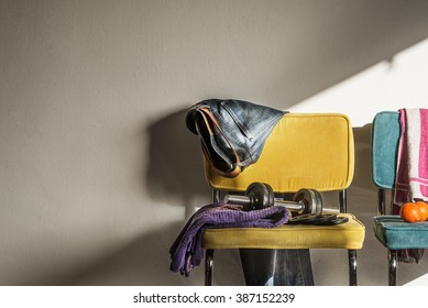 Detail of a teenager's room. Interior sports and gym concept. Dumbbell, towel and jeans on a yellow chair with space for copy.