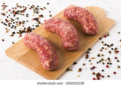 Detail of three sausages on the chopping board on white background, and pepper