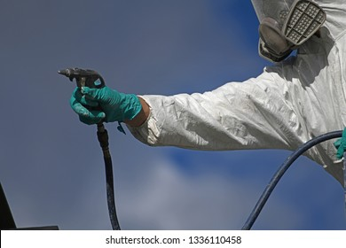 Detail of a tradesman spray painting the steel beams on a construction site