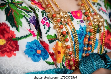 detail of traditional embroidery of folk costume from yucatan mexico, cross stitch with multicolored flowers, gold chains and orange beads with a black background
