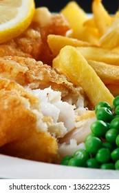 detail of traditional fish and chips with peas and a slice of lemon.