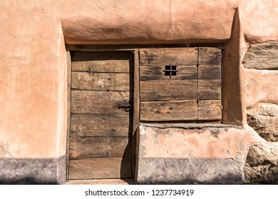 Detail of a traditional house, in the style of Adobe houses, with a wooden door and a small window.