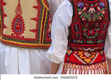 Detail from traditional Romanian folk costumes for men and women with multicolored embroidery.