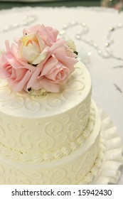 Detail of traditional wedding cake with pink and cream roses.