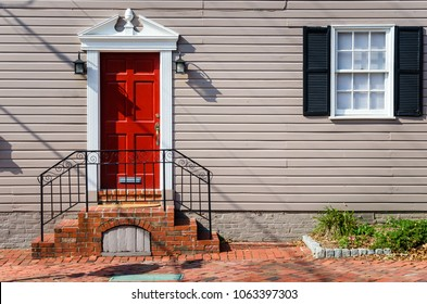 Detail of a Traditional Wooden House with a Red Door and a White Window with Black Shutters along a Brick Sidewalk. Alexandria, VA