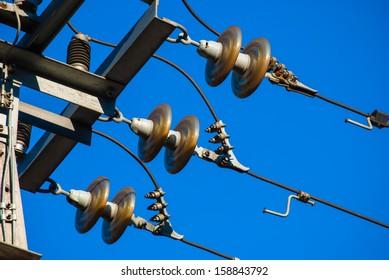 detail of transmission line tower against blue sky