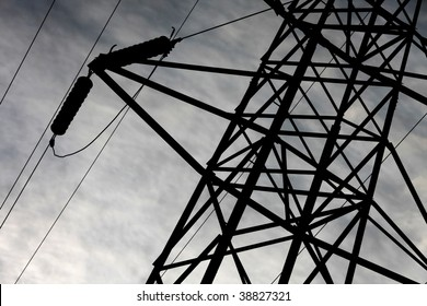 detail of transmission tower with high voltage wires with a moody evening sky in the background