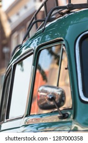 Detail of turquoise and chrome nostalgic car - side mirror, door, window, roof rack - at blurred mirroring town background