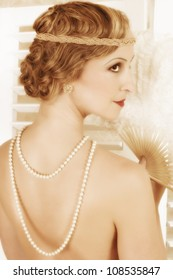 Detail of the twenties hairstyle on an elegant woman with pearls on her nude back