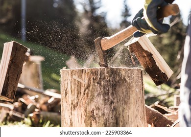 Detail of two flying pieces of wood on log with sawdust. Man is chopping wood with vintage axe. Frozen moment.