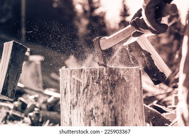 Detail of two flying pieces of wood on log with sawdust. Man is chopping wood with vintage axe. Frozen moment. Black and white photography. Sepia. Cream tone.