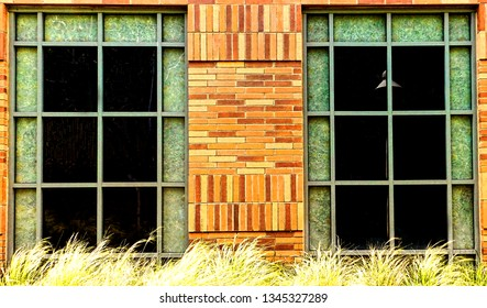 Detail of two green framed windows on an orange, brick building