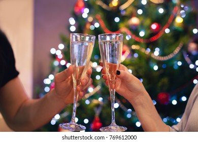 Detail of two hands toasting with wine glasses, in front of a Christmas tree.