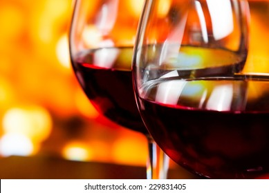 detail of two red wine glasses against colorful unfocused lights background, festive and fun concept