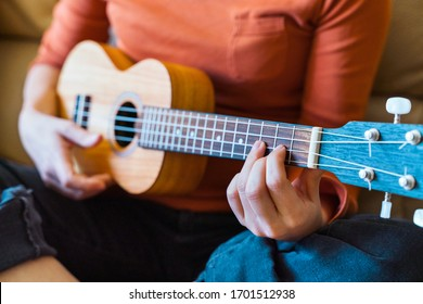 Detail of unrecognizable teacher and student of music lessons. Female professor close up explaining instructions of accurate ukelele chords position on guitar neck with bridge. Spanish guitar concept.