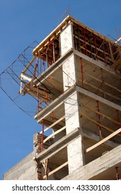 Detail of the upper part of a building under construction on a blue sky background