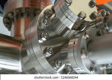 Detail of vacuum equipment with steel flanges bolted to the vessel in laboratory or industrial environment. Abstract industrial or technology background.