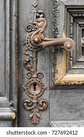 Detail of very ornate metal door handle in the shape of a phoenix with ornate keyhole on worn black wooden door