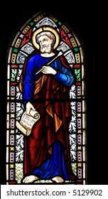 """detail of victorian stained glass church window in Fringford depicting St Luke the Evangelist, a scroll in his hands with the beginning of his gospel in latin """"Fuit in diebus herodes"""""""