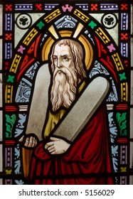 detail of victorian stained glass church window in Fringford depicting Moses with the tablets of covenant in his arms, interestingly without text, means he is pictured before climbing Mount Sinai