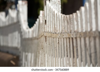 Detail view along an old white picket fence with selective focus