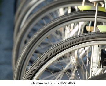 Detail view of a bike wheel with more bicycles lined up behind