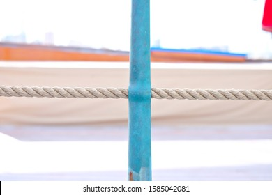 A detail view of a bronze stanchion and a hempen lifeline, details of deck equipment on a classic sailing yacht.