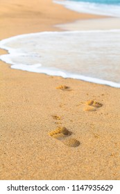 Detail view to footprints in sand at beach shore (copy space)