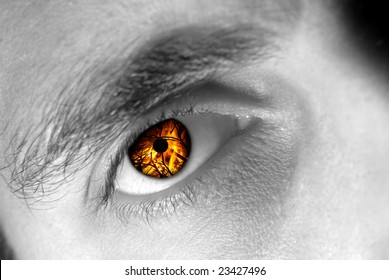 Detail view of a male eye with flames instead of the iris.