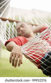 Detail view of a man's relaxed hand while he sleeps on a hammock in the garden.