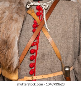 Detail view of a medieval military uniform made from a coarse cloth of gray color. Red buttons or fasteners, leather straps, wild animal furry skin or hide hang across the right shoulder