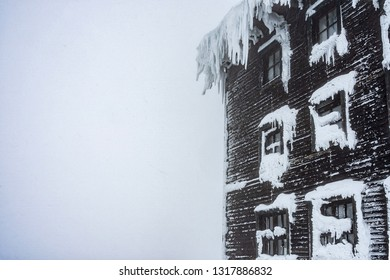 Detail view of mountain cabin in a misty weather. Foggy weather in a snow covered landscape.