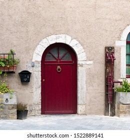 A detail view of an old stone house front in Belgium with a red door and old water pump next to flower beds