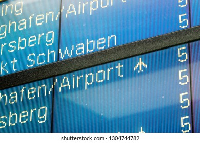 Detail view on English language airplane flight arrival sign with gate number five at side