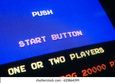 Detail view on old vintage video game with text Push start button, with option to select one or two players